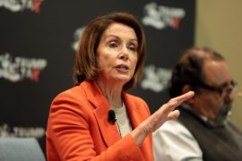 Rep. Nancy Pelosi (D-CA) speaks with her hand raised. She is wearing a bright orange jacket.