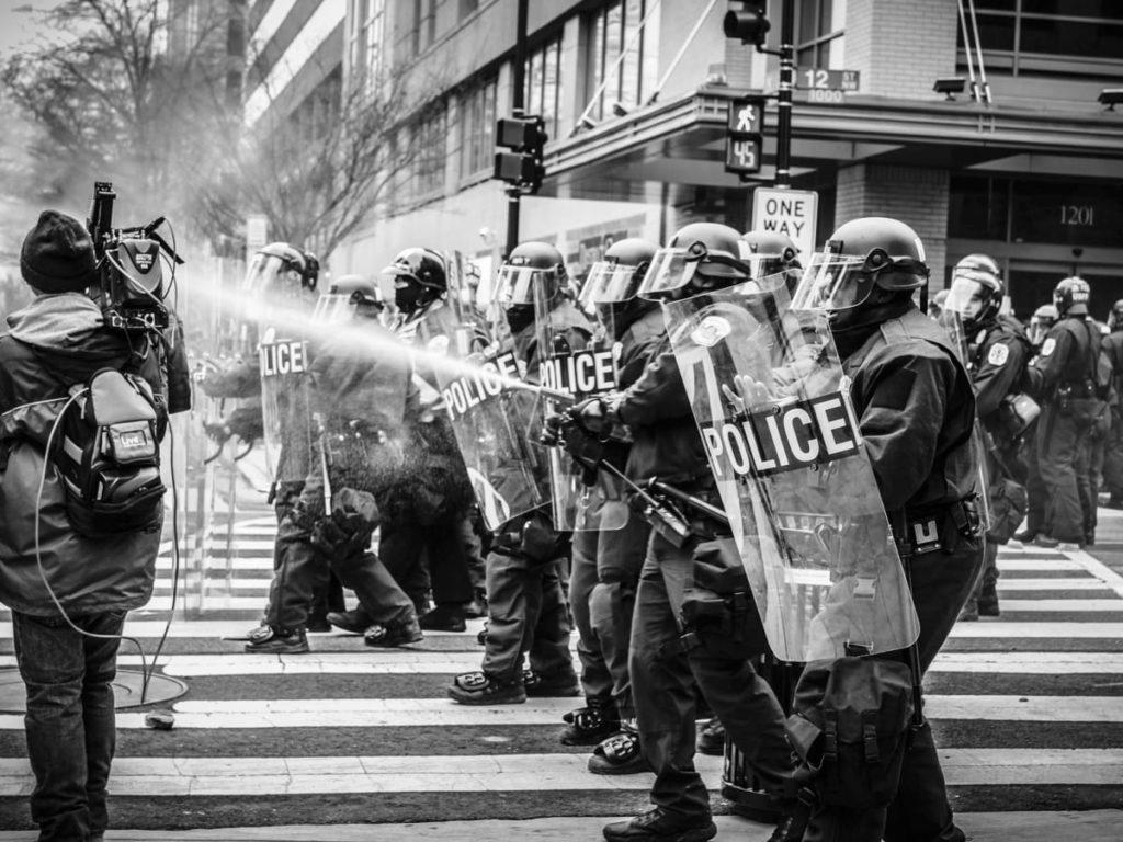 line of police spray a news camera black and white photo