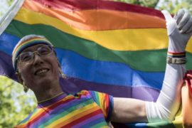 Low angle shot of older Japanese man wearing rainbow outfit and white gloves, rainbow flag behind him