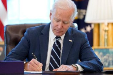 President Biden sitting at desk in White House signing congress COVID relief bill