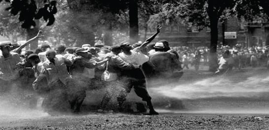 black and white photo of protesters being tear gassed by police