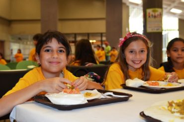 Two girls in orange shirts eating lunch at a table and smiling at the camera