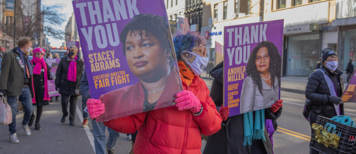 female protester in puffy coat holding up a Stacey Abrams Sign