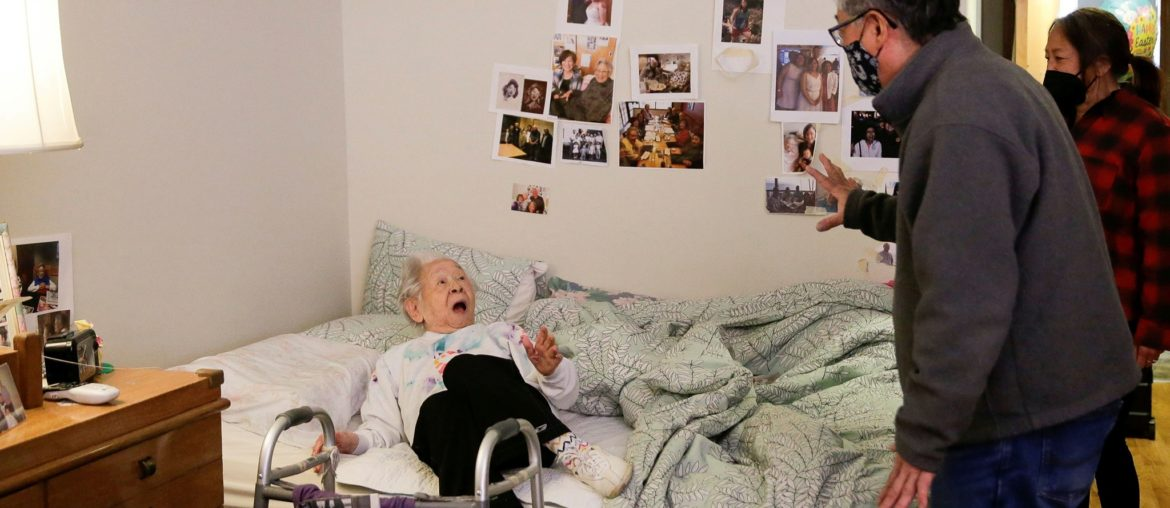 Japanese-American elderly woman in bed looking surprised at a standing man greeting her